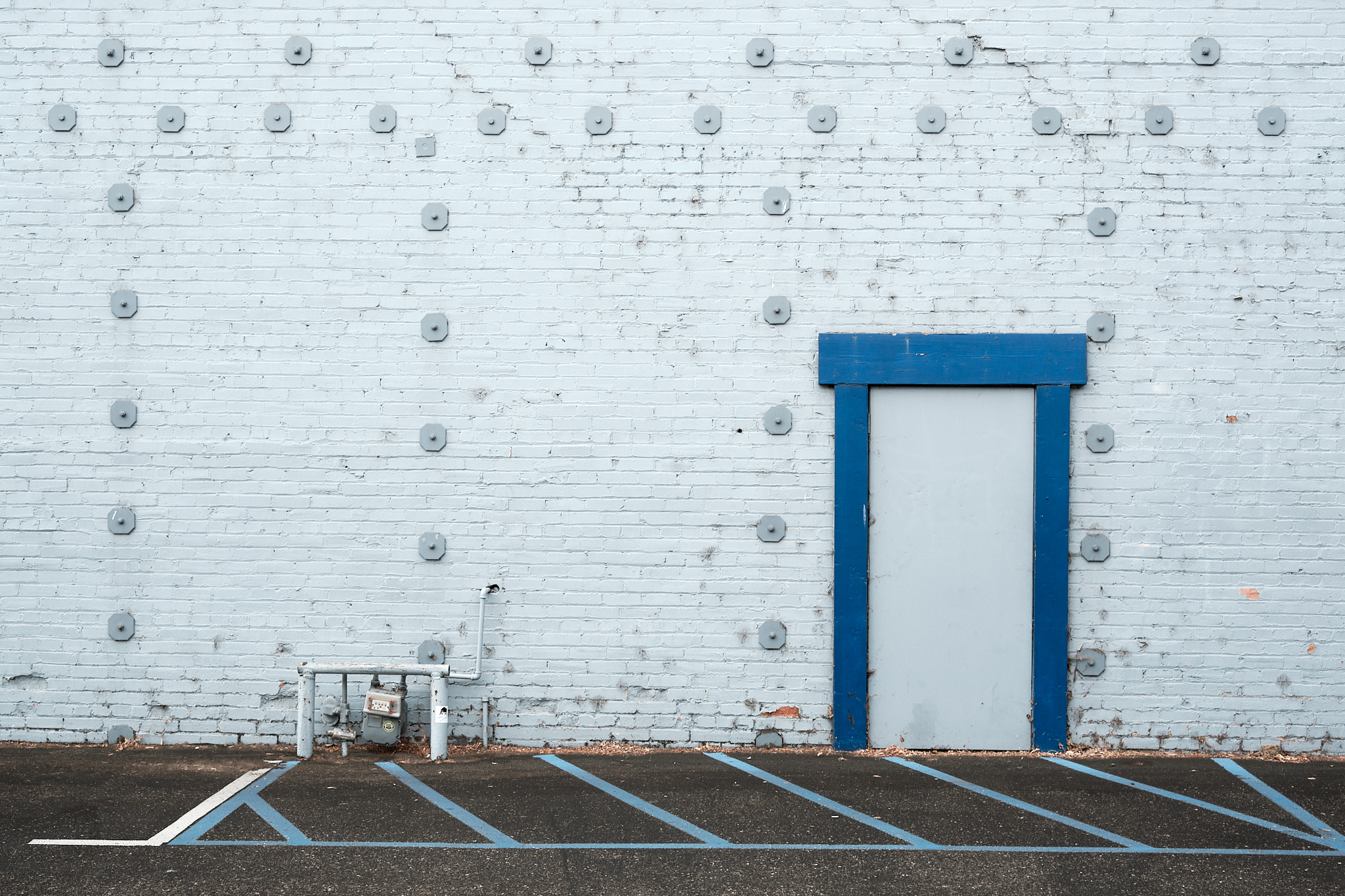 Photograph of door with blue frame and brick wall